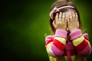 photo of young girl covering her eyes with her hands