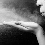 photo of woman blowing dust from her hand