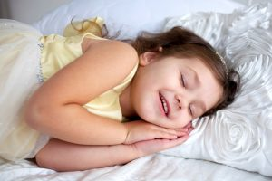 photo of smiling child in bed