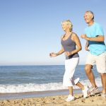 photo of older couple running on beach