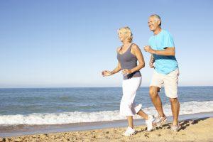 photo of older couple running on beach